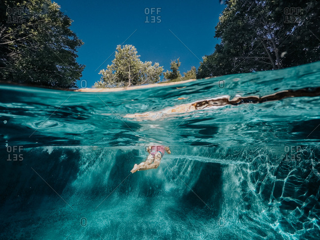 Underwater view of child swimming in pool