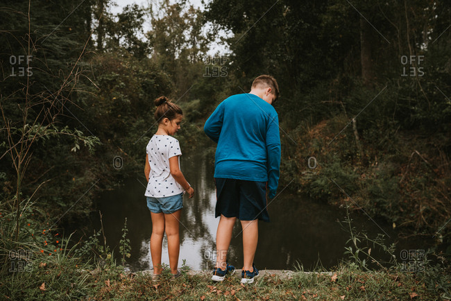 Brother and sister exploring a waterway in the woods