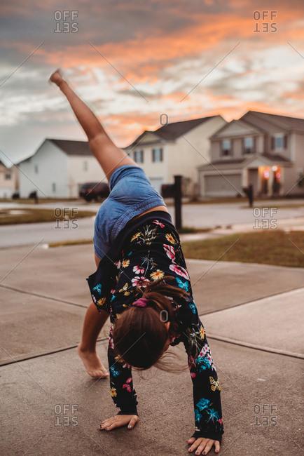 Young girl doing a cartwheel in driveway