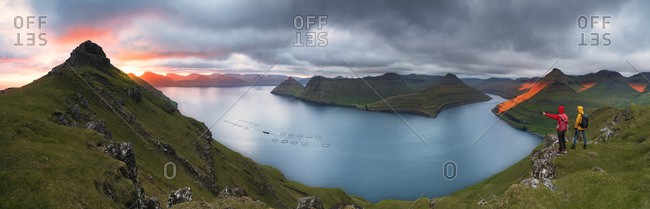 Panoramic of hikers on cliffs looking to the fjords, Funningur, Eysturoy island, Faroe Islands, Denmark, Europe