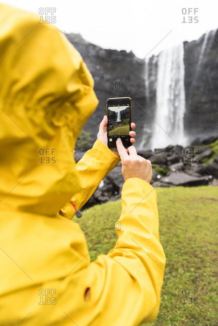 Tourist snaps photos with smartphone, Fossa waterfall, Streymoy island, Faroe Islands, Denmark, Europe