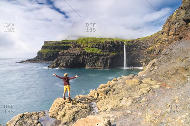 July 3, 2018: Man on cliffs with open arms admiring Gasadalur waterfall, Vagar island, Faroe Islands, Denmark, Europe