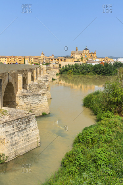 September 2, 2018: Puente Romano (Roman bridge) along Guadalquivir River with Mezquita Cathedral in background, Cordoba, UNESCO World Heritage Site, Andalusia, Spain, Europe