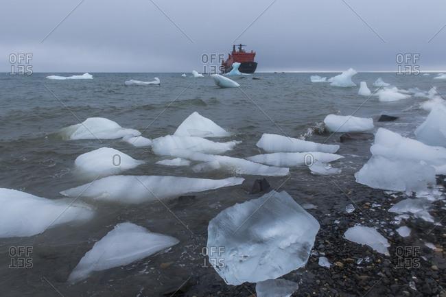 August 8, 2018: Icebreaker anchoring behind an iceberg, Champ Island, Franz Josef Land archipelago, Arkhangelsk Oblast, Arctic, Russia, Europe