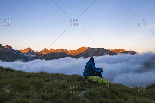 July 26, 2017: A hiker watches the sunset on the Pyrenees and a cloud inversion near Refuge Pombie along the GR10 trekking route, Pyrenees Atlantiques, France, Europe