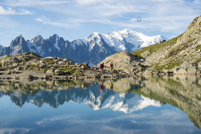 Hikers and the summit of Mont Blanc reflected in Lac Blanc on the Tour du Mont Blanc trekking route in the French Alps, Haute Savoie, Auvergne-Rhone-Alpes, France, Europe