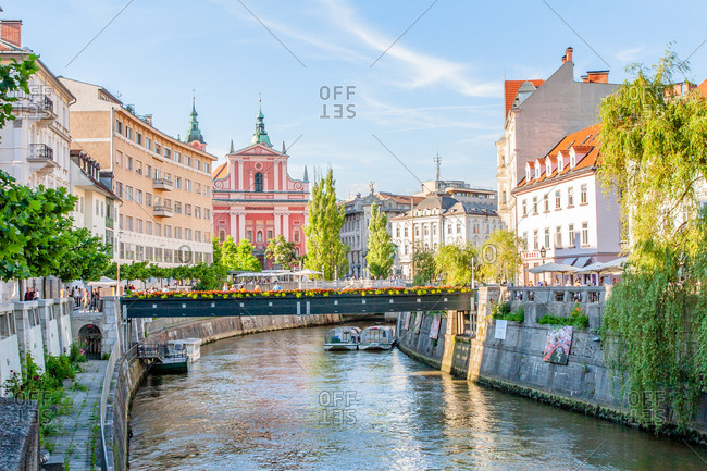 June 19, 2008: Looking down the Sava River to the pink 17th century Franciscan Church, Ljubljana, Slovenia, Europe