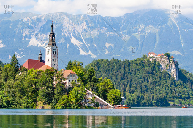 Tiny island with a church, a castle on a crag, and mountain views, Lake Bled, Slovenia, Europe