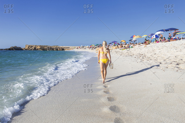 September 23, 2018: Young girl in a yellow swimsuit walks on the beach of Is Arutas, Cabras, Oristano province, Sardinia, Italy, Mediterranean, Europe