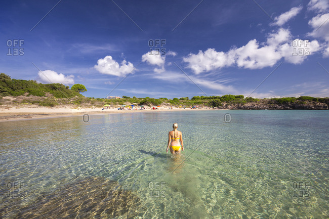 A girl in swimsuit walks in the water, La Bobba Beach, San Pietro Island, Sud Sardegna province, Sardinia, Italy, Mediterranean, Europe