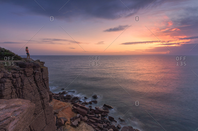 A girl looks at sunset from a cliff, Sant'Antioco Island, Sud Sardegna province, Sardinia, Italy, Mediterranean, Europe