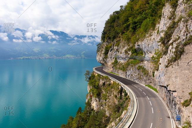 A curved road built into the side of a mountain next to Lake Thun, Interlaken, Bernese Oberland, Bern, Switzerland, Europe