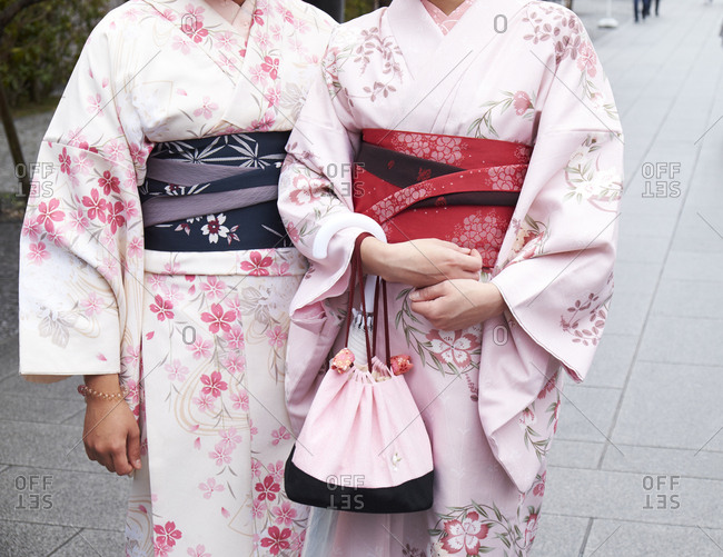 Fushimi Inari-Taisha, Kyoto Prefecture, Japan- April 5, 2017: Two women dressed in Kimonos pose for a photo, cutaway