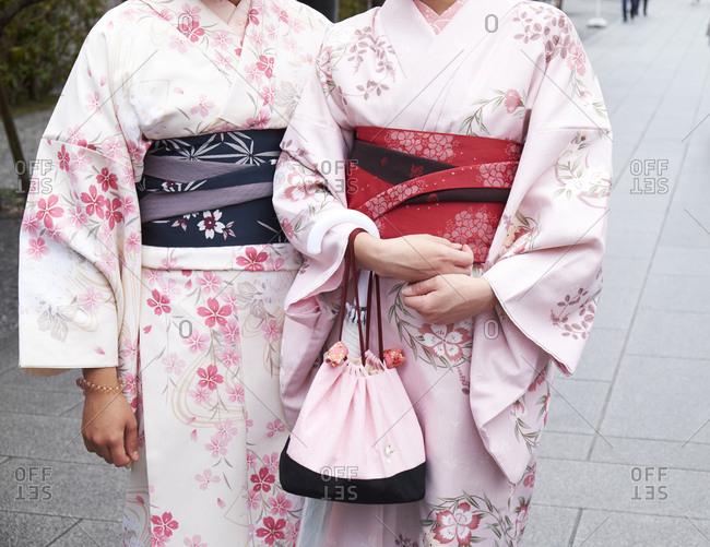 Fushimi Inari-Taisha, Kyoto Prefecture, Japan- April 5, 2017: Two women dressed in Kimonos pose for a photo, cutaway