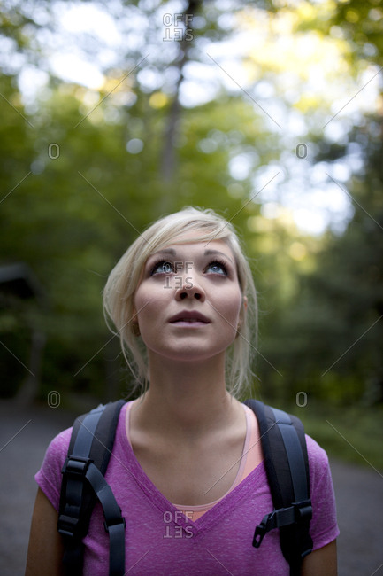 Young woman hiking up to the top of a mountain alone