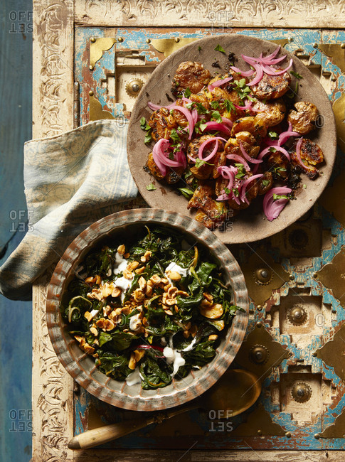 Chermoula smashed potatoes with pickled onion and a kale salad with yogurt and nuts