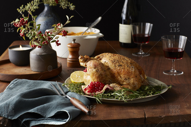 Roasted chicken on a table for Thanksgiving dinner with pomegranate and lemon