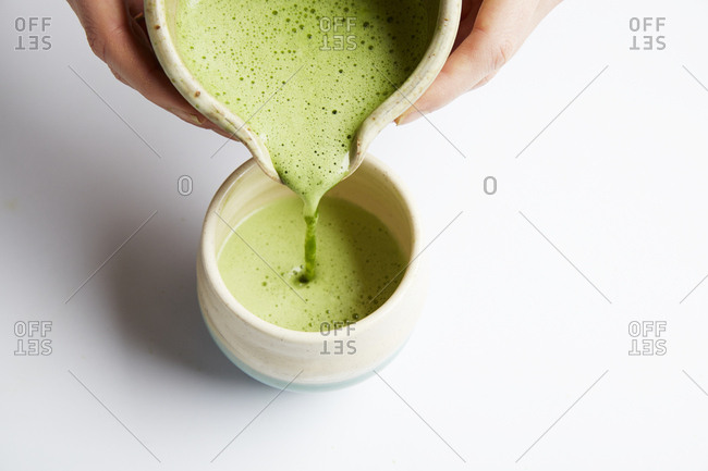 Hands pouring matcha drink being poured