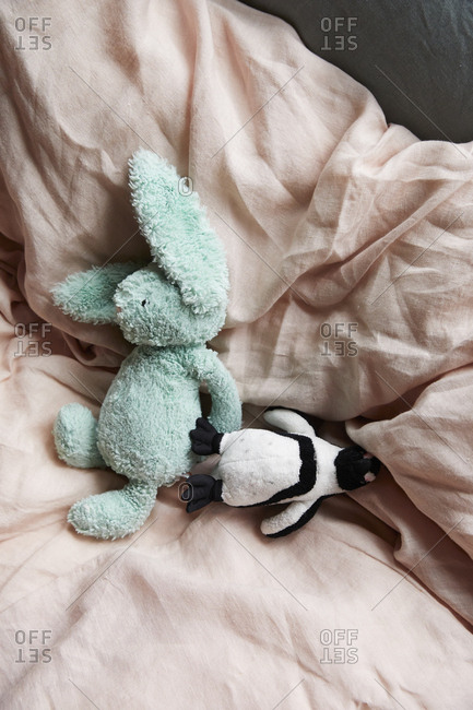 Stuffed animals on a cozy bed