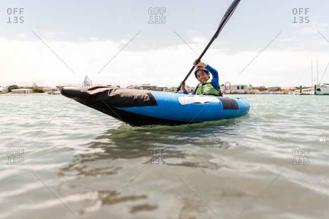 Boy paddling in a blue kayak near Hawke's Bay, New Zealand