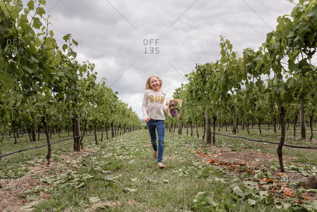Blonde girl walking in a vineyard carrying flowers