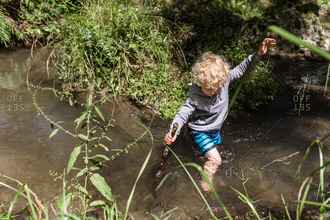 Curly haired boy walking in creek with a stick