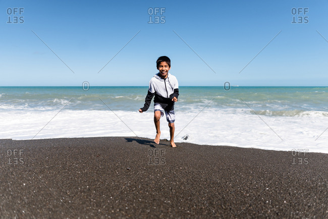 Young boy running on a beach in Hawke's Bay, New Zealand