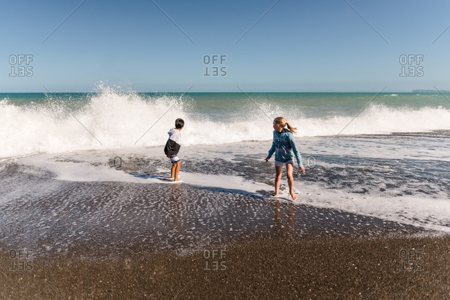 Two kids running from waves