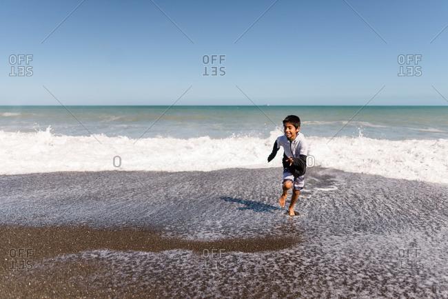 Boy running on a beach in Hawke's Bay, New Zealand