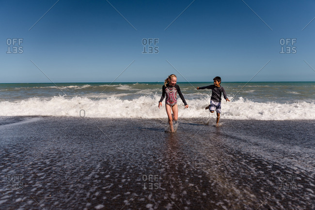 Two kids running from waves on a beach in Hawke's Bay, New Zealand