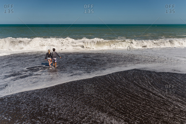 Two kids playing in waves on a beach in Hawke's Bay, New Zealand