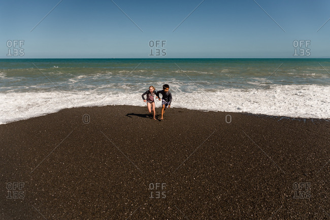 Two kids running from waves on a beach in New Zealand