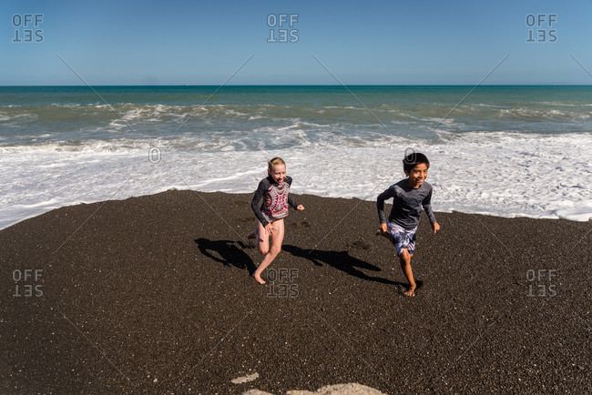 Kids running from waves on a beach in New Zealand