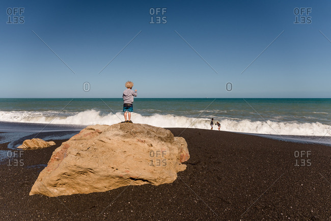 Little boy watching from a rock as older siblings play in the waves on a beach