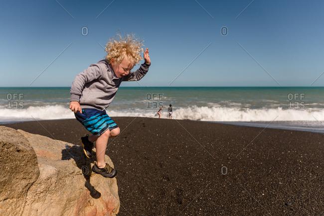 Little boy jumping from a rock on a beach