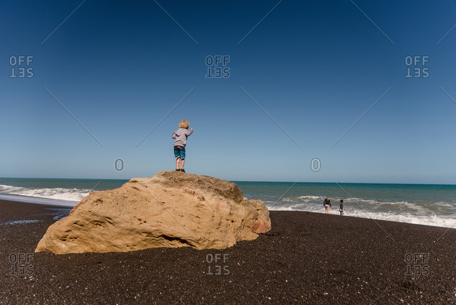 Little boy watching from a rock as older kids play in the waves on a beach