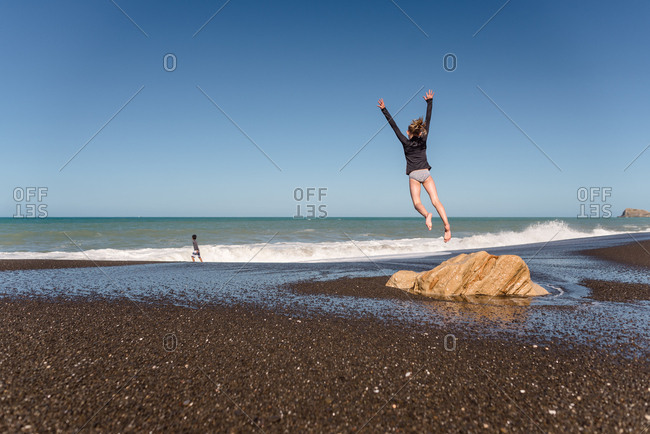 Girl leaping from rock on a beach in New Zealand