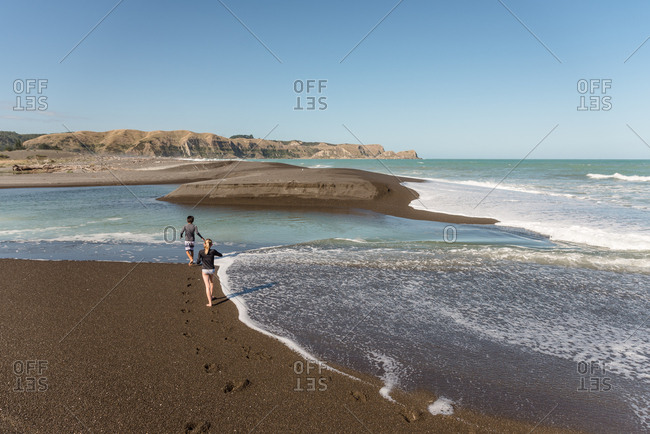 Girl and boy walking on a beach in New Zealand