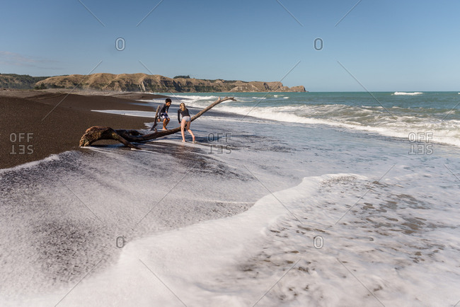 Kids climbing on driftwood on a beach in New Zealand