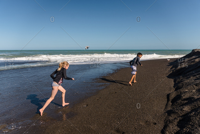 Girl chasing boy on a beach in New Zealand