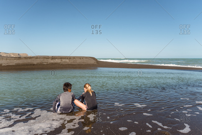 Girl and boy sitting in the water on a beach in New Zealand