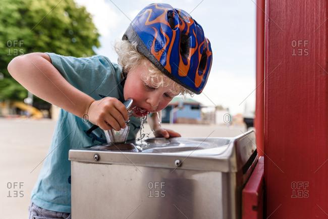 Little boy wearing bike helmet drinking from fountain