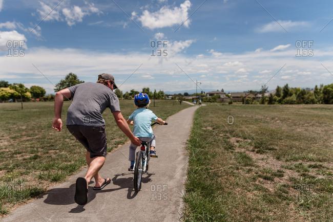 Father helping little boy ride bike