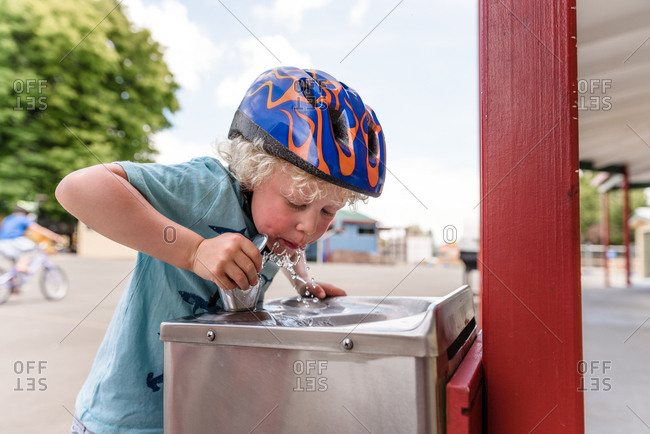 Blonde boy wearing bike helmet drinking from fountain