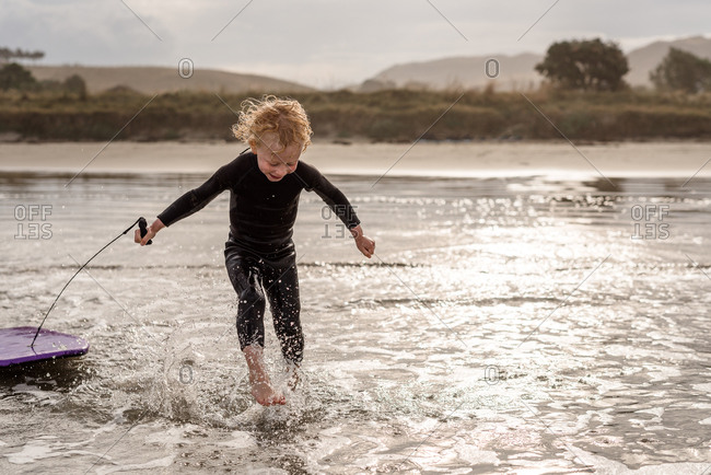 Young boy running in ocean with boogie board