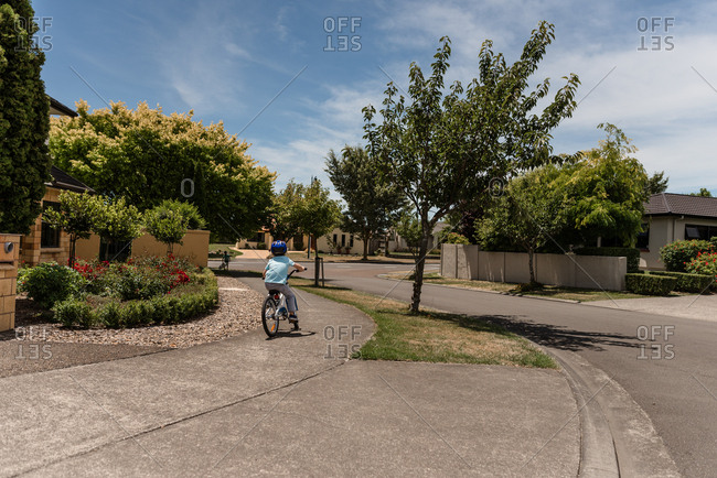 Boy riding bike on residential sidewalk