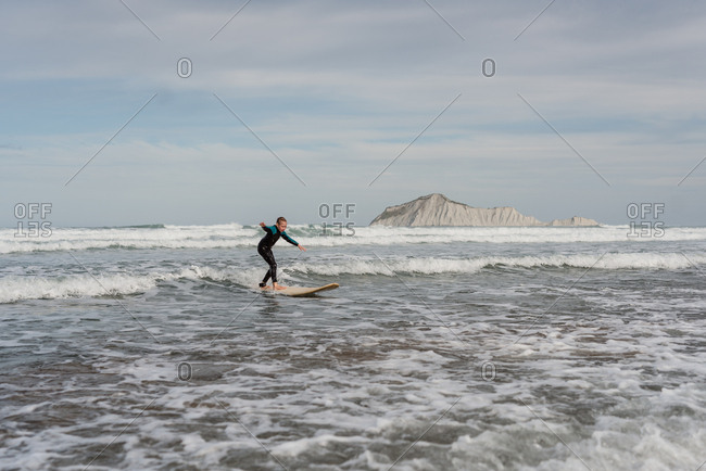 Girl surfing on the coast of New Zealand