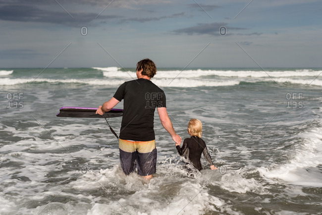 Father and son in the ocean with a boogie board