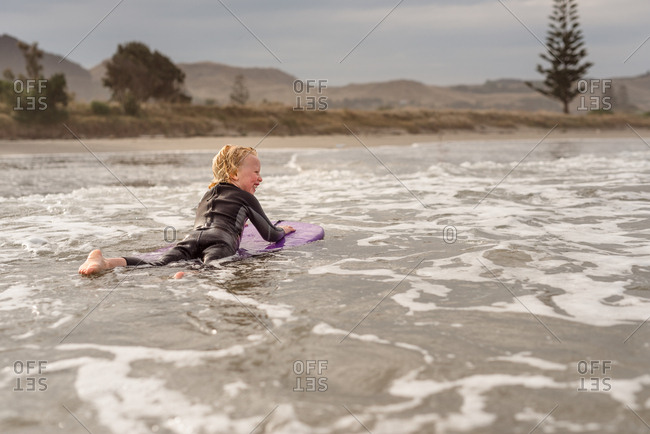 Young boy riding on a boogie board in the ocean