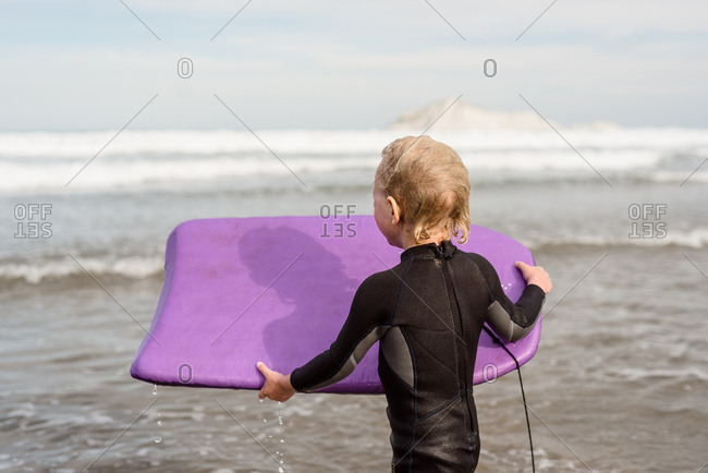 Young boy in the ocean with boogie board